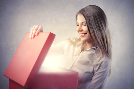 Happy beautiful woman opening a gift